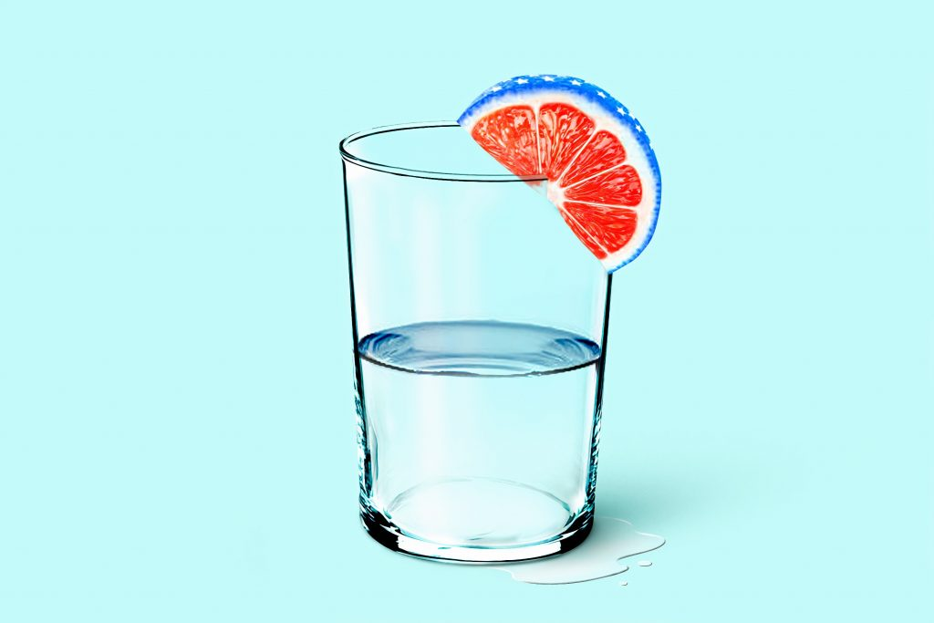 This image is showing a glass half full and a piece of red orange. The photo is a courtesy of Morning Brew on Unsplash.